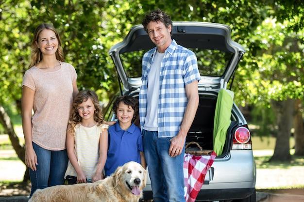 Familia sonriente de pie delante de un coche