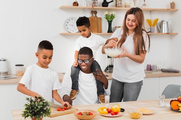 Familia sonriente preparando la cena juntos