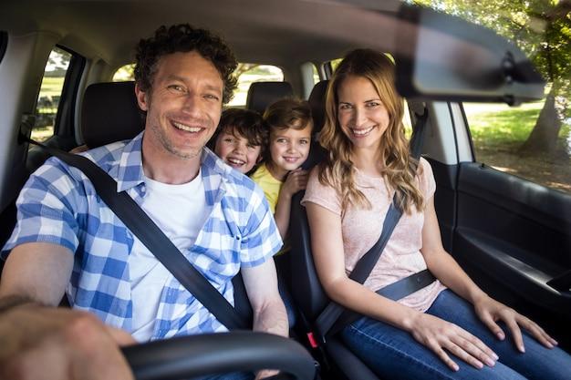 Familia sonriente sentada en el auto