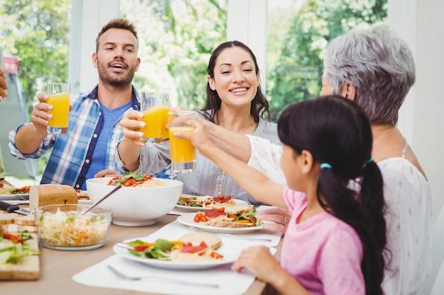 Familia sonriente tintineando con vaso de jugo