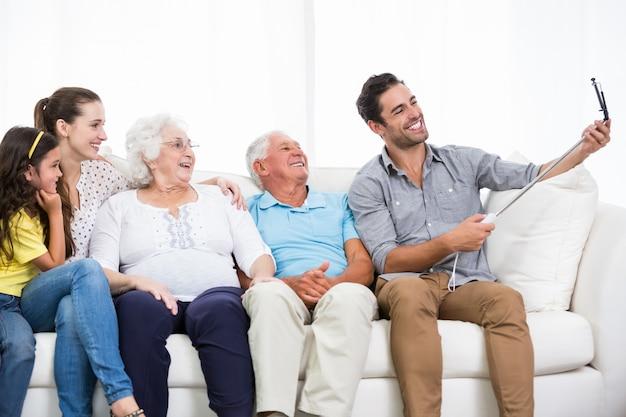 Familia sonriente tomando autorretrato mientras está sentado en el sofá