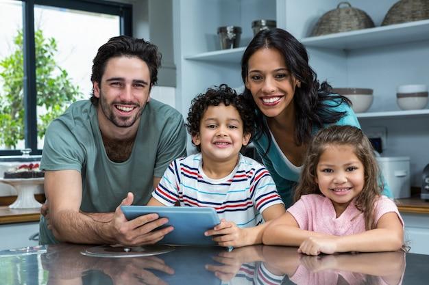 Familia sonriente usando tableta en la cocina