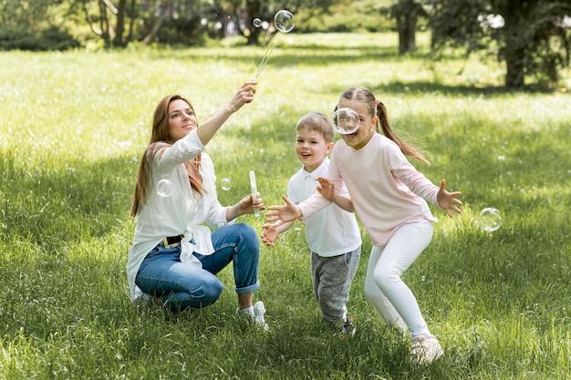 Familia soplando burbujas en el parque