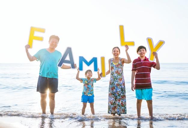 Familia sosteniendo cartas en la playa