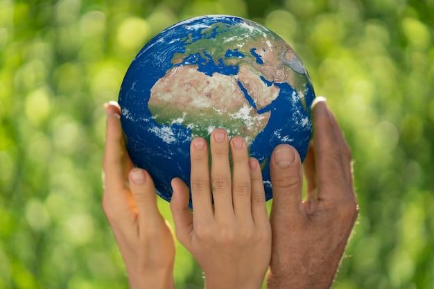 Familia sosteniendo el planeta 3d en las manos. guante de tierra. salva nuestro planeta