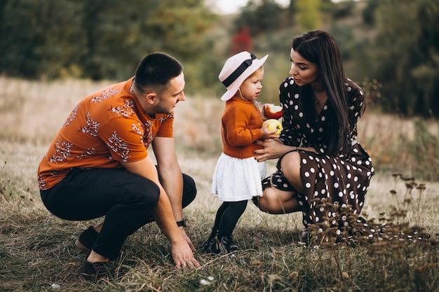 Familia con su pequeña hija en un bosque de otoño