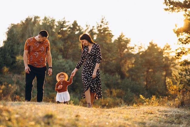 Familia con su pequeña hija en un campo de otoño