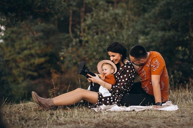 Familia con su pequeña hija haciendo un picnic en un campo