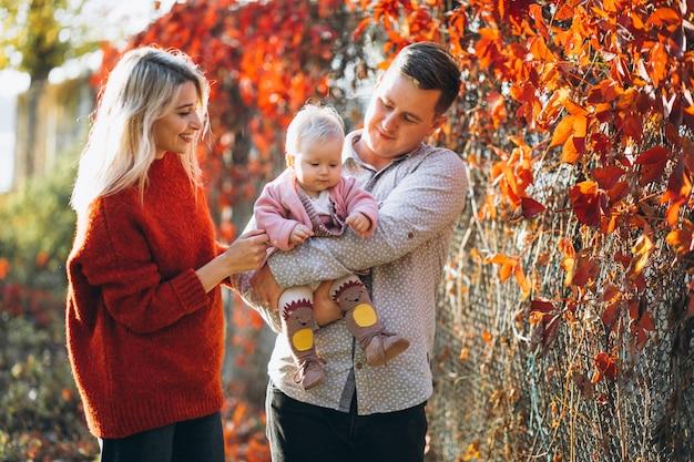 Familia con su pequeña hija en un parque de otoño