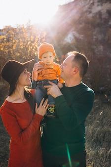 Familia con su pequeño hijo en un parque de otoño