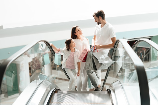 La familia está subiendo las escaleras mecánicas en el centro comercial.