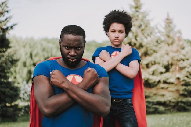 Familia de superhéroes, manos plegadas con rostro serio.