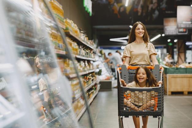 Familia en el supermercado. mujer con camiseta marrón. la gente elige productos. madre con hija.
