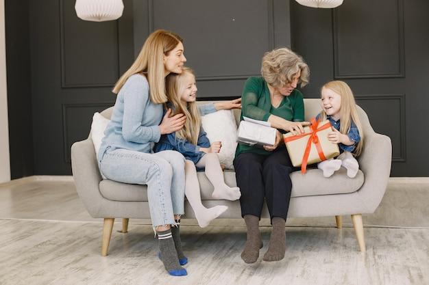Familia y sus dos hijas celebran cumpleaños. dos mujeres y dos niñas sentadas en un sofá.