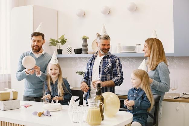 La familia y sus dos hijas tienen una celebración. gente soplando globos. los presentes están sobre la mesa.