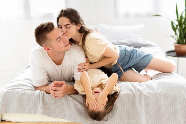 Familia teniendo un lindo momento juntos en el dormitorio
