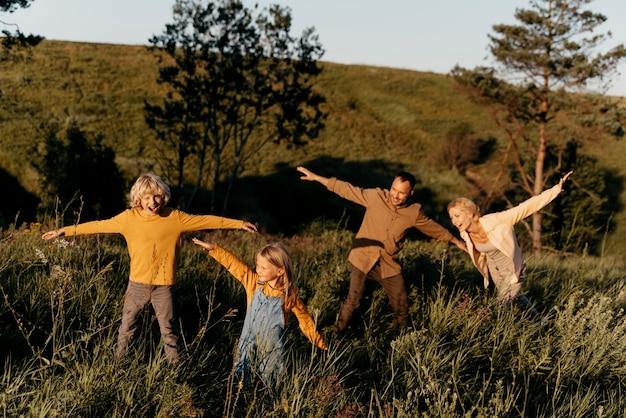 Familia de tiro completo divirtiéndose en la pradera