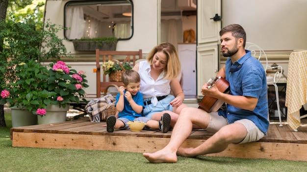 Familia de tiro largo disfrutando de música de guitarra