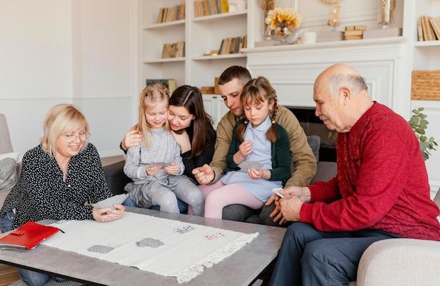 Familia de tiro medio jugando a las cartas juntos