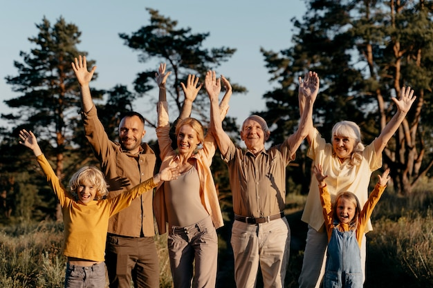 Familia de tiro medio con las manos arriba