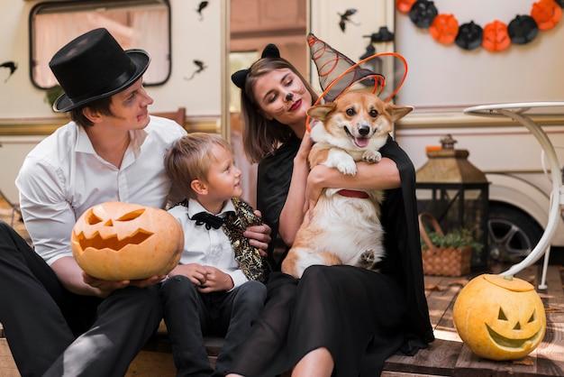Familia de tiro medio con perro con sombrero