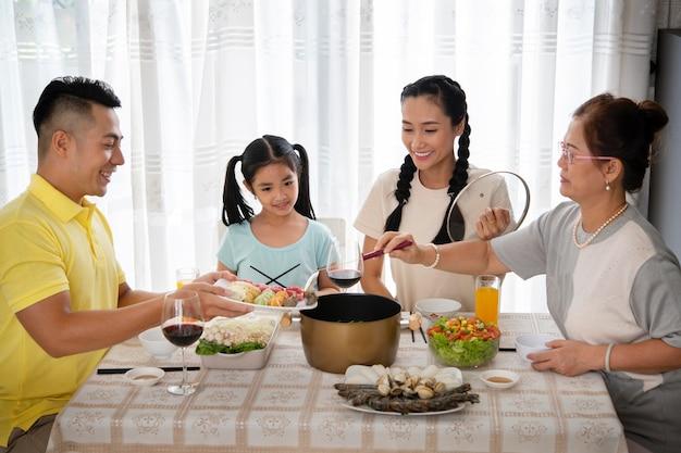 Familia de tiro medio sentado en la mesa