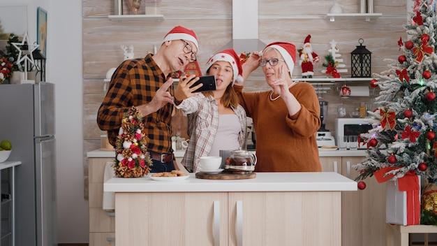Familia tomando selfie con smartphone disfrutando de las vacaciones de invierno en la cocina decorada de navidad