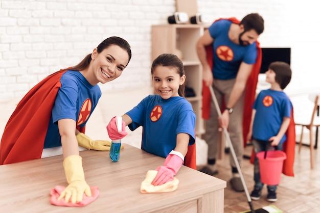 La familia en trajes de superhéroes se limpia en casa.