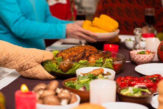 Familia trayendo comida a la mesa de acción de gracias