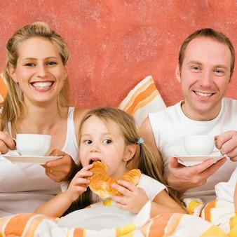 Familia de tres en la cama desayunando