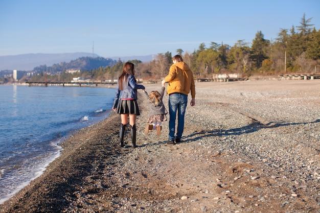 Familia de tres cerca del mar negro en día soleado de invierno
