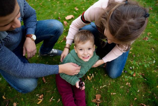 Familia de tres disfruta el parque de otoño divirtiéndose sonrisa
