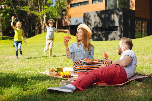 Familia unida. mujer bonita alegre sentada con su marido y sus hijos jugando