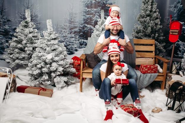 Familia unida en navidad en bosque artificial bajo nevadas