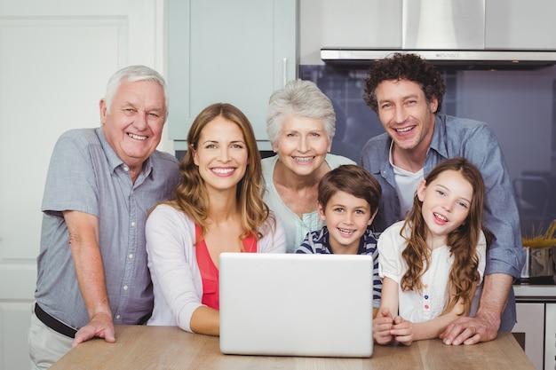 Familia usando una computadora portátil en la cocina