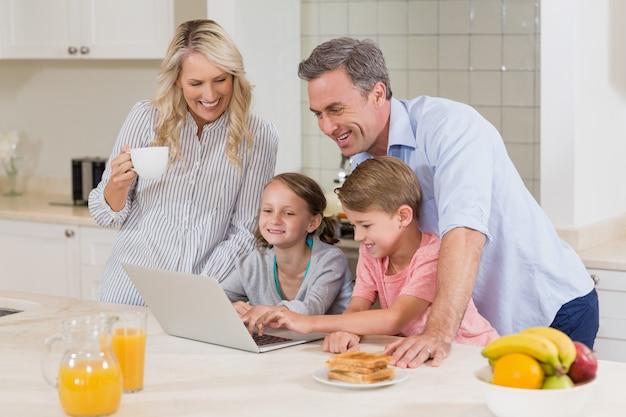 Familia usando una computadora portátil mientras desayuna en la cocina