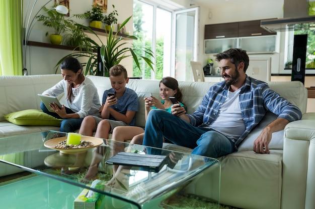 Familia usando una computadora portátil y un teléfono móvil en la sala de estar