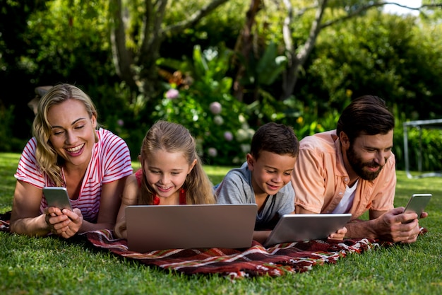 Familia usando tecnologías mientras está acostado en el patio
