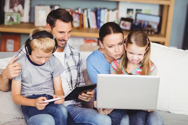 Familia usando tecnologías en el sofá