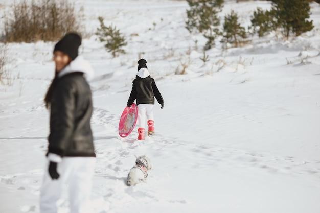 Familia en vacaciones familiares de navidad. mujer y niña en un bosque. la gente camina.