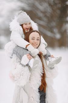 Familia en vacaciones familiares de navidad. mujer y niña en un parque. la gente camina.