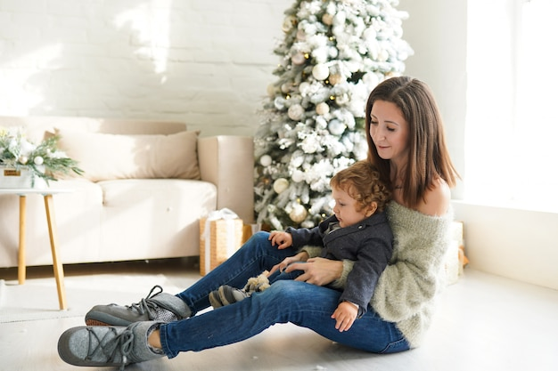 Familia, vacaciones de invierno y concepto de personas - feliz madre y bebé cerca del árbol de navidad en casa
