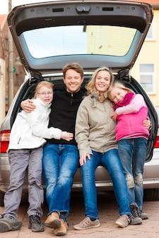 Familia en un viaje en auto sentada en la parte de atrás