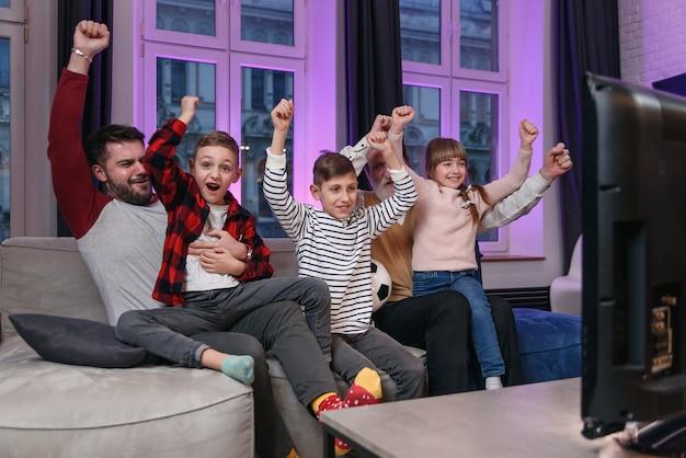 Familia viendo partido de fútbol americano, campeonato en el sofá en casa. fans que animan emocionalmente al equipo nacional favorito. niños con padre y abuelo disfrutando de ocio en casa.