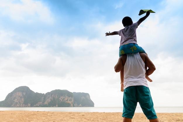 Familia con vista al mar, o padre e hijo están felices con los viajes y el picnic con vistas al mar.