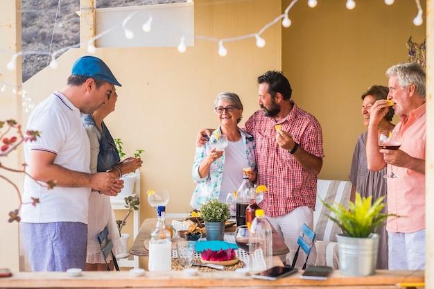 Familiares y amigos almorzando todos juntos en casa en la terraza