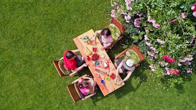 Familiares y amigos comiendo juntos al aire libre en la fiesta en el jardín de verano. vista aérea de mesa con comida y bebida desde arriba. concepto de ocio, vacaciones y picnic.