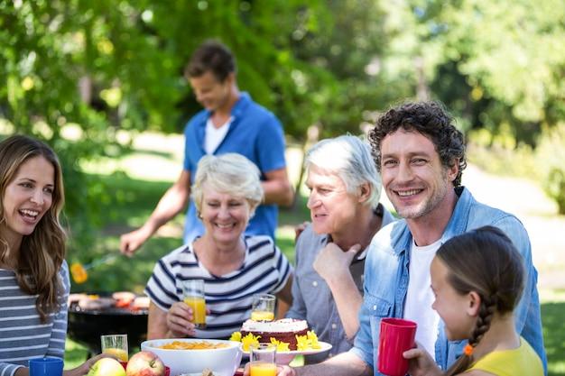 Familiares y amigos haciendo un picnic con barbacoa.
