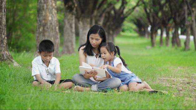 Familias asiáticas hacen actividades juntas leyendo libros en el parque alegremente