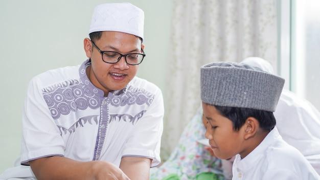 Las familias musulmanas asiáticas leen el corán después de las oraciones